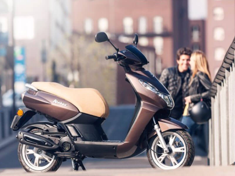 joli scooter marron et beige, devant un couple